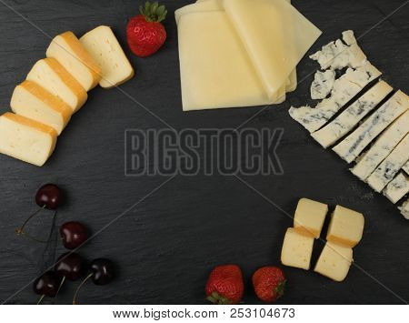 Cheeseboard With Sliced Cheese Top View On Black Stone Plate Background