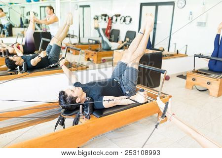 Active Fit Young Man Doing Exercise On Pilates Reformer In Health Club