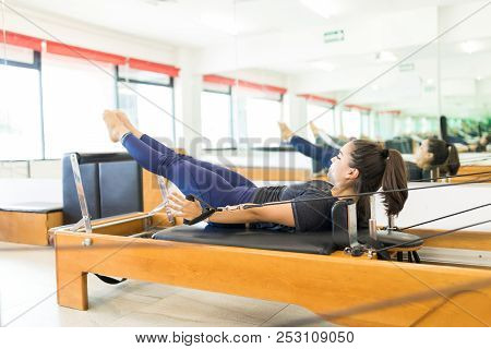 Full Length Of Determined Woman Pulling Resistance Bands On Pilates Reformer In Health Club