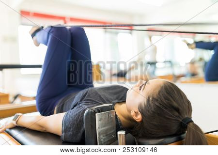 Full Length Of Body Conscious Woman Exercising On Pilates Reformer Machine In Gym