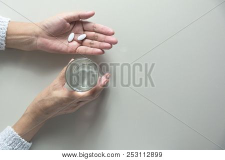 Taking Medicine Pills. Woman Holds In Hands The Medicine Pills And A Glass Of Water.  Healthcare Con