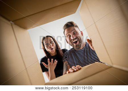 The Surprised Man And Woman Unpacking, Opening Carton Box And Looking Inside. The Package, Delivery,