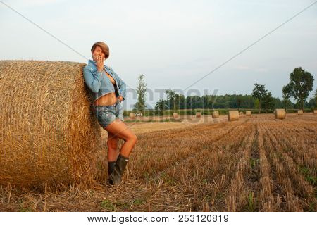 Sexy young woman posing on the field near a haystack