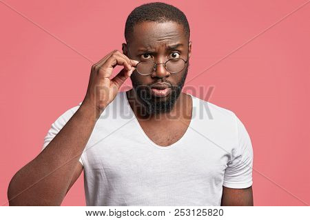 Serious Dark Skinned Male Professor Looks In Bewilderment Through Spectacles, Feels Angry With Bad S
