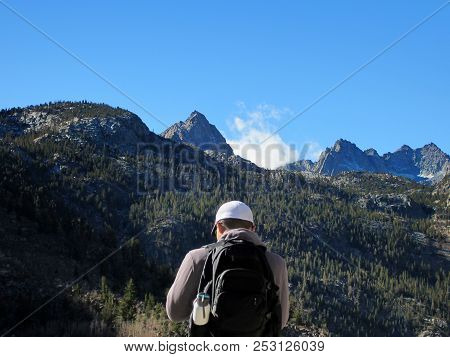 Male Hiker Pauses And Enjoys The Picturesque Sunny Scenery During A Hike Near Lake Sabrina In Inyo C