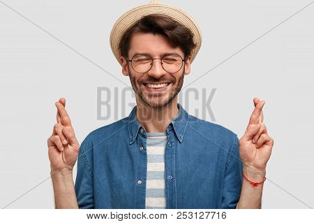 Glad Young Caucasian Male With Pleasant Smile, Crosses Fingers As Believes In Better, Wears Casual C