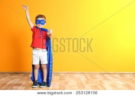 Adorable Little Child Playing Superhero On Color Background. Indoor Recreation