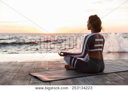 Image of strong young fitness woman outdoors in the beach make yoga meditate exercises.