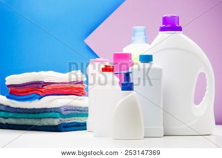 Photo of bottles of cleaning products and colored towels on table isolated on blue, purple background