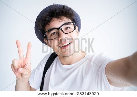 Self Portrait Of Happy Male Student Enjoying Vacation. Cheerful Mixed Race Guy In Glasses And Summer