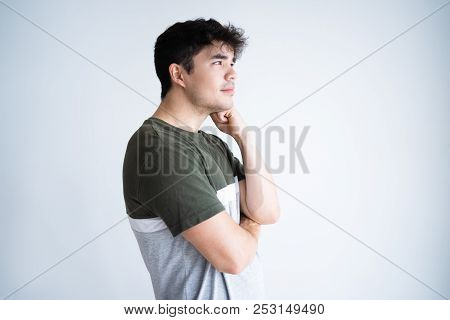 Side Portrait Of Pensive Positive Curly Guy Leaning Chin On Hand. Young Mixed Race Man Thinking Over