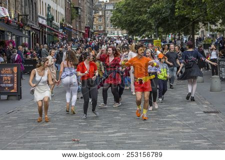 Edinburgh, Scotland  - August 7: A Jubilant Group Dances On The Sidewalk At The Edinburgh Fringe Fes