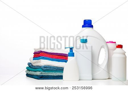 Photo of bottles of cleaning products and multi-colored cloths on clean white background