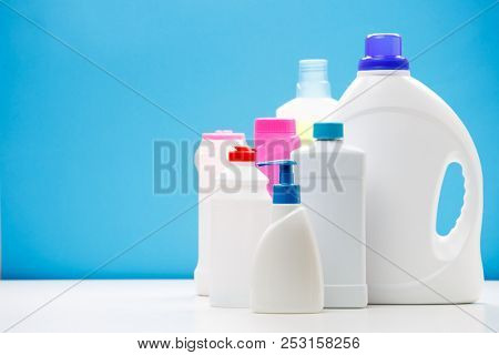 Photo of bottles of cleaning products on white table isolated on blue background