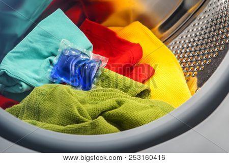 blue gel caps in washing mashine, liquid coloured detergent