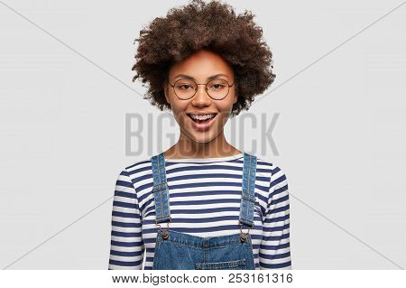 Black Cheerful Curly African American Female Happy To Finish Successful Project, Dressed In Casual S