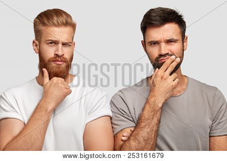 Indoor Shot Of Pensive Thoughtful Concentrated Two Men Hold Chins, Try To Find Right Solution Or Mak
