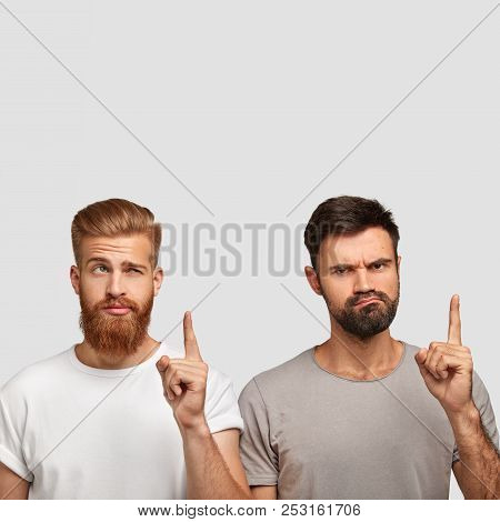 Photo Of Handsome Bearded Ginger Male And His Discontent Gloomy Friend Point Upwards With Index Fing