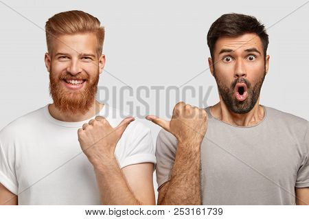 Cheerful Ginger Male In High Spirit Indicates At His Companion With Surprised Expression, Wear Casua