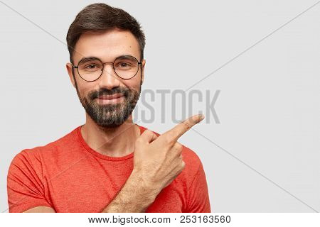 Photo Of Pleased Unshaven European Male With Cheerful Expression, Has Thick Stubble, Points Aside, S