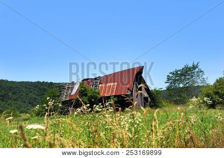 Arkansas Barn, In The Ozark Mountains, Has Torn Tin Roof That Is Rusting And Worn.  Boards Are Broke