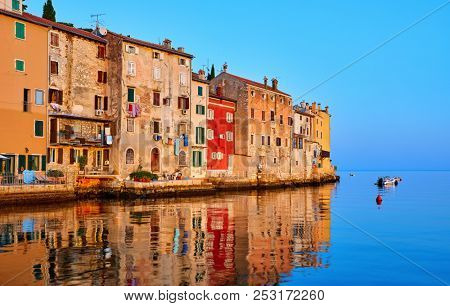 Rovinj, Istria, Croatia. Antique medieval houses at coastline of Adriatic sea. Sunrise with blue sky and fishing boat on horizon. Calm and silent summer morning.