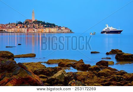 Rovinj, Istria, Croatia. Antique medieval old town at Adriatic sea. Calm summer morning with blue sky. Panorama with nighttime illumination. View at chapel of Church of Saint Euphemia. Luxury yacht.