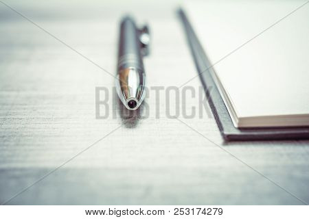 Biro Beside An Empty Notepad On A Table