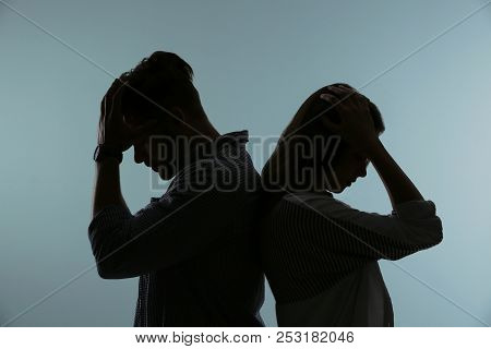 Silhouette Of Upset Couple On Color Background. Relationship Problems