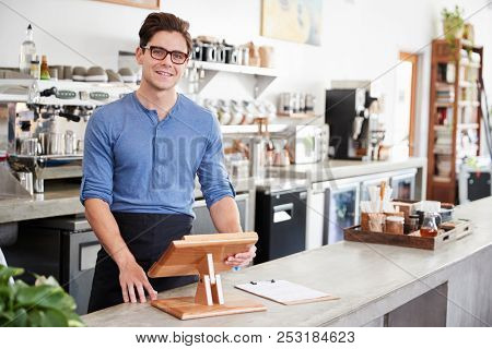 Male coffee shop owner behind the counter at his coffee shop