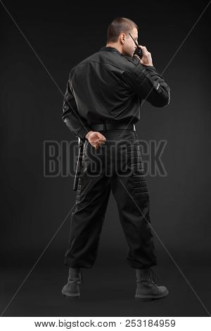 Male Security Guard Using Portable Radio Transmitter On Dark Background