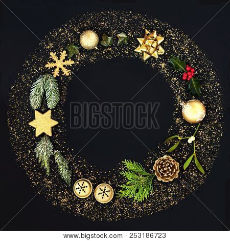Christmas wreath garland with gold glitter, bauble decorations and winter flora on black background.Top view. Festive Christmas card for the holiday season.