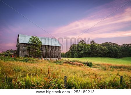 A Barn In The Countryside With Tall Grass And Trees At Sunset.