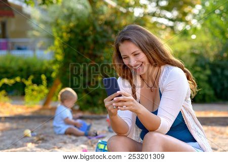 Vivacious Young Mother Laughing At A Text Message On Her Mobile Phone As She Sits Outdoors In A Play