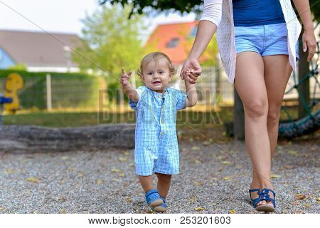 Happy Little Baby Boy Walking With His Mother Or Babysitter Outdoors In A Playground In A Low Angle