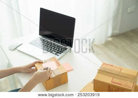 Shipping Shopping Online,young Start Up Small Business Owner Writing Address On Cardboard Box At Wor