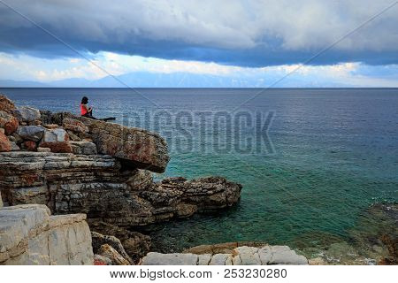 A Woman Alone Rests On The Rocks On The Beach. She Dreams About The Future And Looks Into The Distan