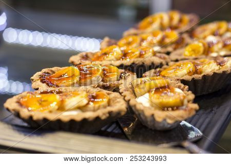Tartlets With Fresh Bananas On A Black Tray