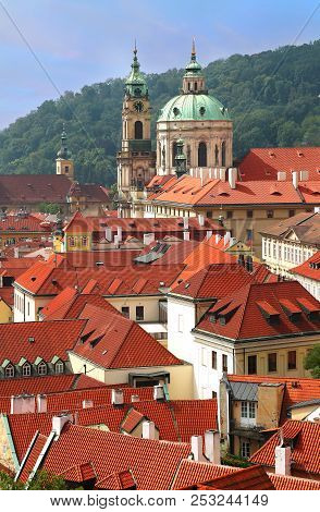 St Nicholas Church Dome Above Red Roof Tops Of Mala Strana And Petrin Hill As Backdrop In Prague, Cz