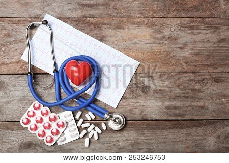 Stethoscope, Cardiogram And Pills On Wooden Background. Cardiology Service
