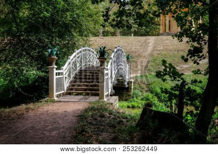 Romantic White Bridge Over A Small Brook In The Forest As A Background