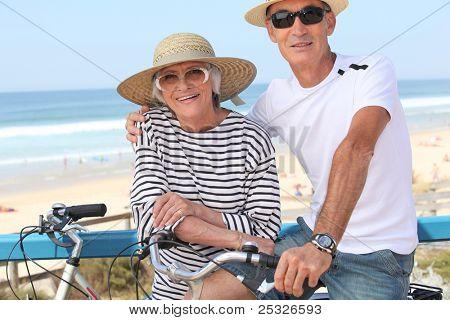 Senior couple riding bikes by the ocean