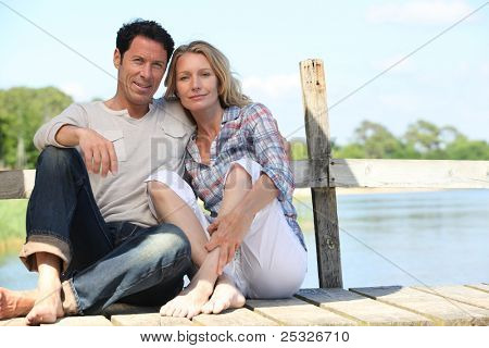 mid age couple seated on a pontoon near a lake