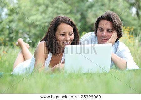 Paar liegen auf dem Rasen, Blick auf einem Laptop-Computer-Bildschirm