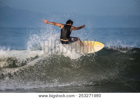 Male Surfer Glides Across The Wave Lip And Across To The Next Section In The Warm Water Sent From Hu