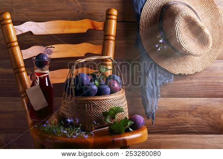 Ripe Plums In A Wicker Basket On A Wooden Chair