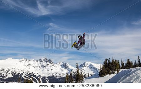 Snowboarder In Mid-air Grabbing The Back Of His Board.