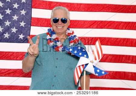 a man celebrates America in a Photo Booth. American Man in an American Flag Holiday Photo Booth.
