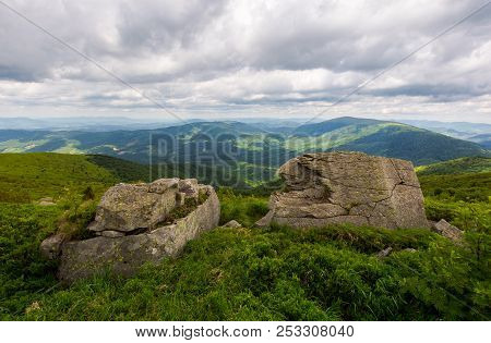 Two Boulders On The Grassy Hill. Mountain Range In The Distance. Overcast Sky In Summer