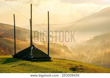 Empty Hay Barrack On A Hill Side. Beautiful Foggy Scenery In The Distant Valley. Rural Lifestyle